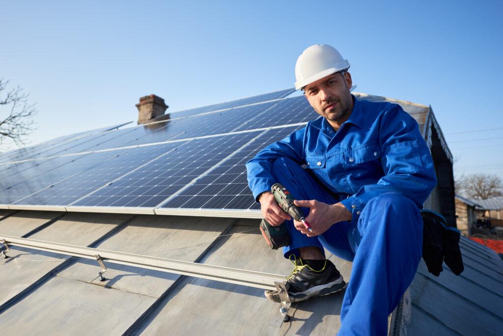 Porträt eines männlichen Handwerkers im blauen Anzug mit Schutzhelm, der ein Solar-Photovoltaik-Paneelsystem installiert. und zur Kamera schaut und auf dem Dach sitzt. Modernes Haus mit alternativem energieökologischem Konzept.