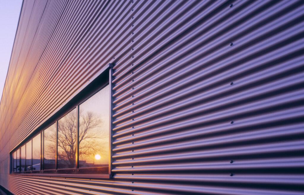 Sonnenuntergang spiegelt sich auf der Metallfassade eines neu errichteten Firmenlagers.