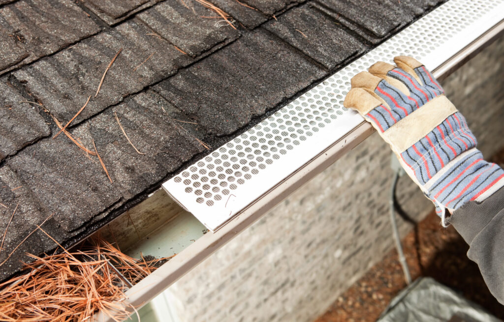 Ein Arbeiter mit Handschuhen montiert einen Blattschutz für Dachrinnen auf einem Hausdachs. Der perforierte Kunststoff und das Netz verhindern, dass Blätter die Dachrinne verstopfen. Dadurch muss weniger oft die Dachrinne gereinigt werden. Der ganz linke Teil der Dachrinne ist mit Kiefernholz-Nadeln verstopft, die rechte Seite wurde gereinigt, was zu nassen Schindeln in diesem Bereich führte.